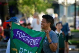 """Sept. 21, 2013 — Isaura Medez, right, holds a peace flag at the International Day of Peace gathering at the Boston Common on Saturday afternoon. Medez encourages peace and forgiveness. At the rally, she said, """"Hate destroys you."""" Photo by Lisa Dukart."""