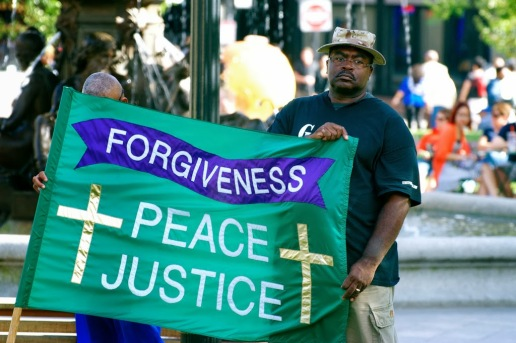 """Sept. 21, 2013 — Reverend Rodney E. Dailey, right, holds a peace flag at the International Day of Peace gathering at the Boston Common on Saturday afternoon. Dailey, who promotes peace in gangs, and is the founder of Gang Peace in Boston, said, """"We can bring the peace. It is in us."""" Photo by Lisa Dukart."""